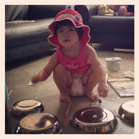 At 22 months, Hannah requests for her hat before her drumming session.